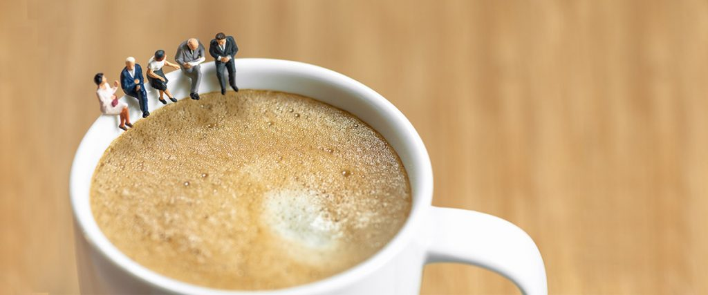 coffee cup with miniature people sitting on rim, metaphor for this guest post about ordering a cup of coffee when meeting with customers