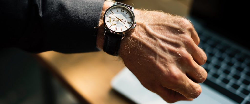 man's arm, with a focus on his wrist and closed hand to highlight the watch as a metaphor for the elevator pitch