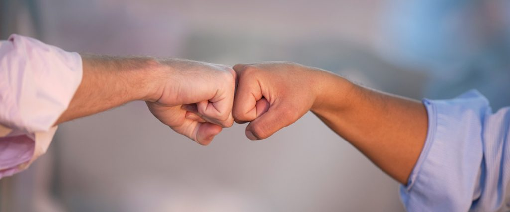 two executives connecting with a fist bump, arms and fists are only visible, demonstrate good body language