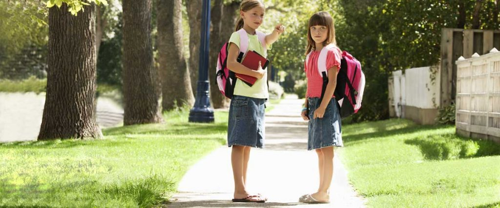 two 8 year old girls, walking home from school, on the sidewalk, pointing with a wave
