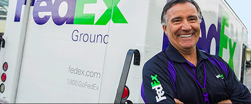 fedex home delivery truck with smiling driver, arms crossed, in a comfortable and natural pose, demonstrating outstanding customer service