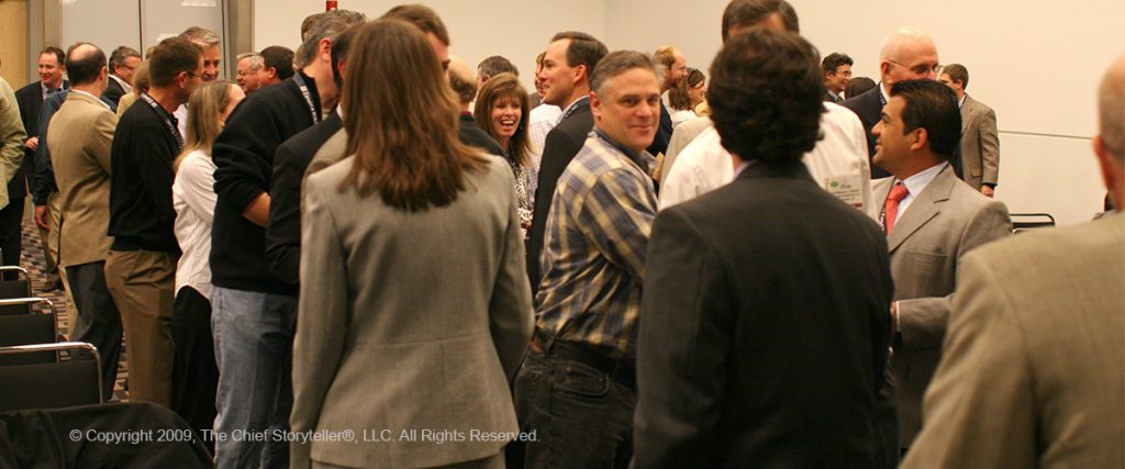 room full of executives networking, shaking hands, talking, sharing his or her elevator pitch