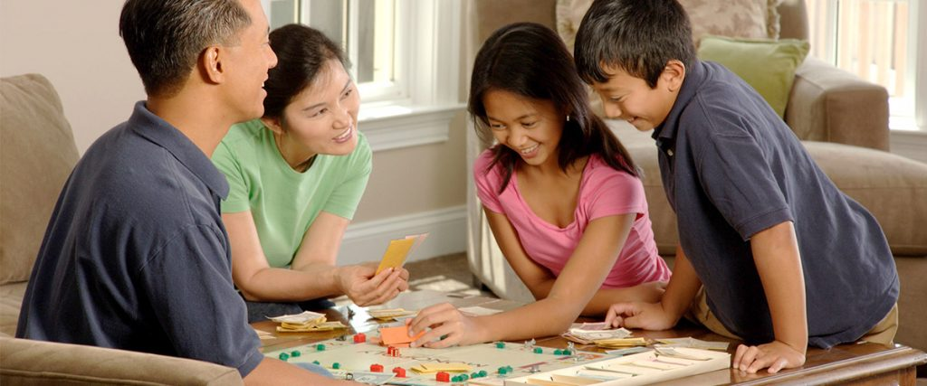 family, father, mother, son, daughter, playing monopoly sharing lessons on life in living room - lessons learned on sales