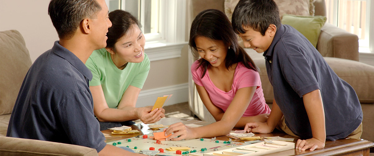 family, parents, son, daughter, playing monopoly sharing lessons on life in living room