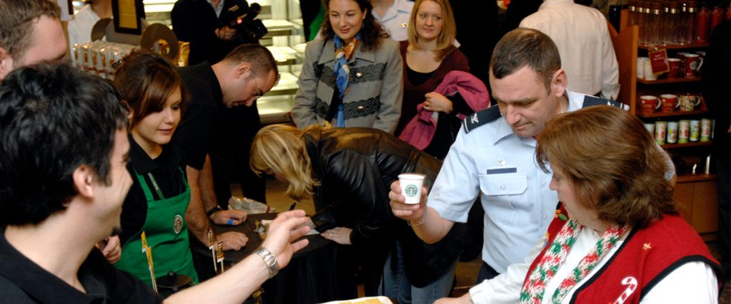 starbucks opening in US Air Force base, filled with happy customers eating and drinking