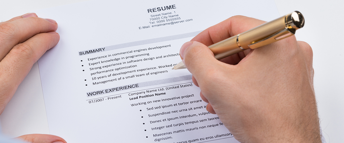 standard resume, right hand with pen over the resume about to write