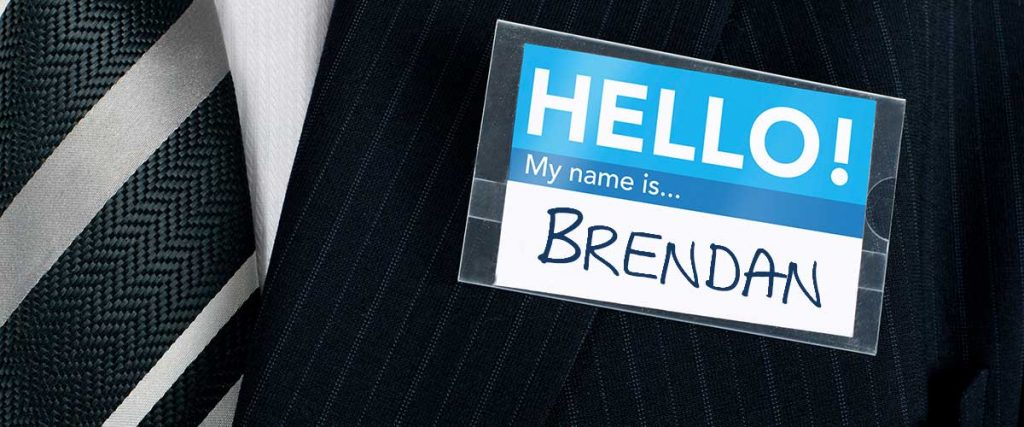 executive at networking event, wearing suit and tie, with the Brendan hand written on the name tag