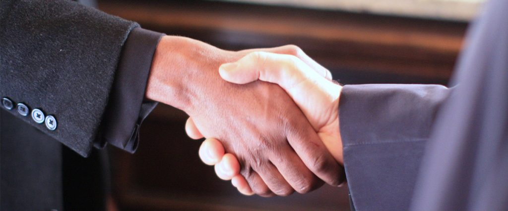 two male executive shaking hands - handshake should never be noticeable