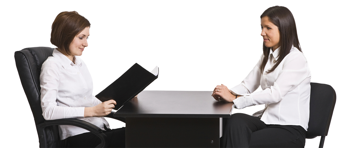 two women sitting a table with one interviewing the other, mid thirties in age