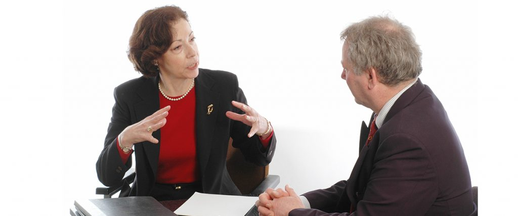 two executives having a meeting around a table, female executive is gesturing and talking to male executive