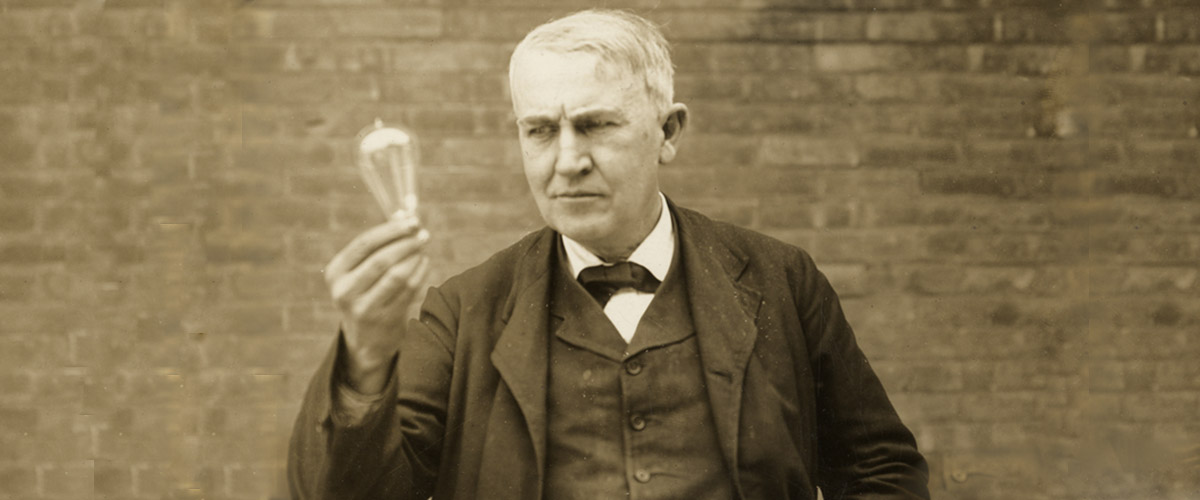 thomas alva edison circa 1910, holding lightbulb up in his right hand