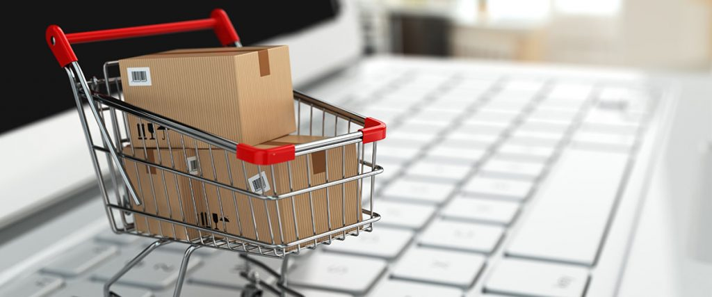 miniature shopping cart with packages on top of a laptop keyboard for email marketing strategy