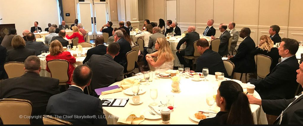 networking lunch, professional executives in suits, listening to guest speaker, sit with strangers to meet new people