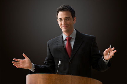 executive male, suit with red tie, behind a podium, smiling, arms spread wide