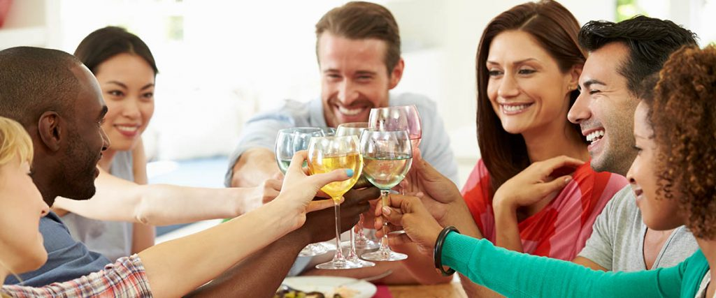 group of friends celebrating, multi-ethnic, 30 to 40 somethings, clinking wine glasses, relationship building