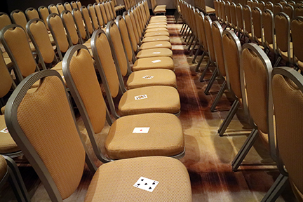 long row of seats before Ira Koretsky's keynote, with a playing card on each chair, for his Treat Everyone Like a CEO exercise