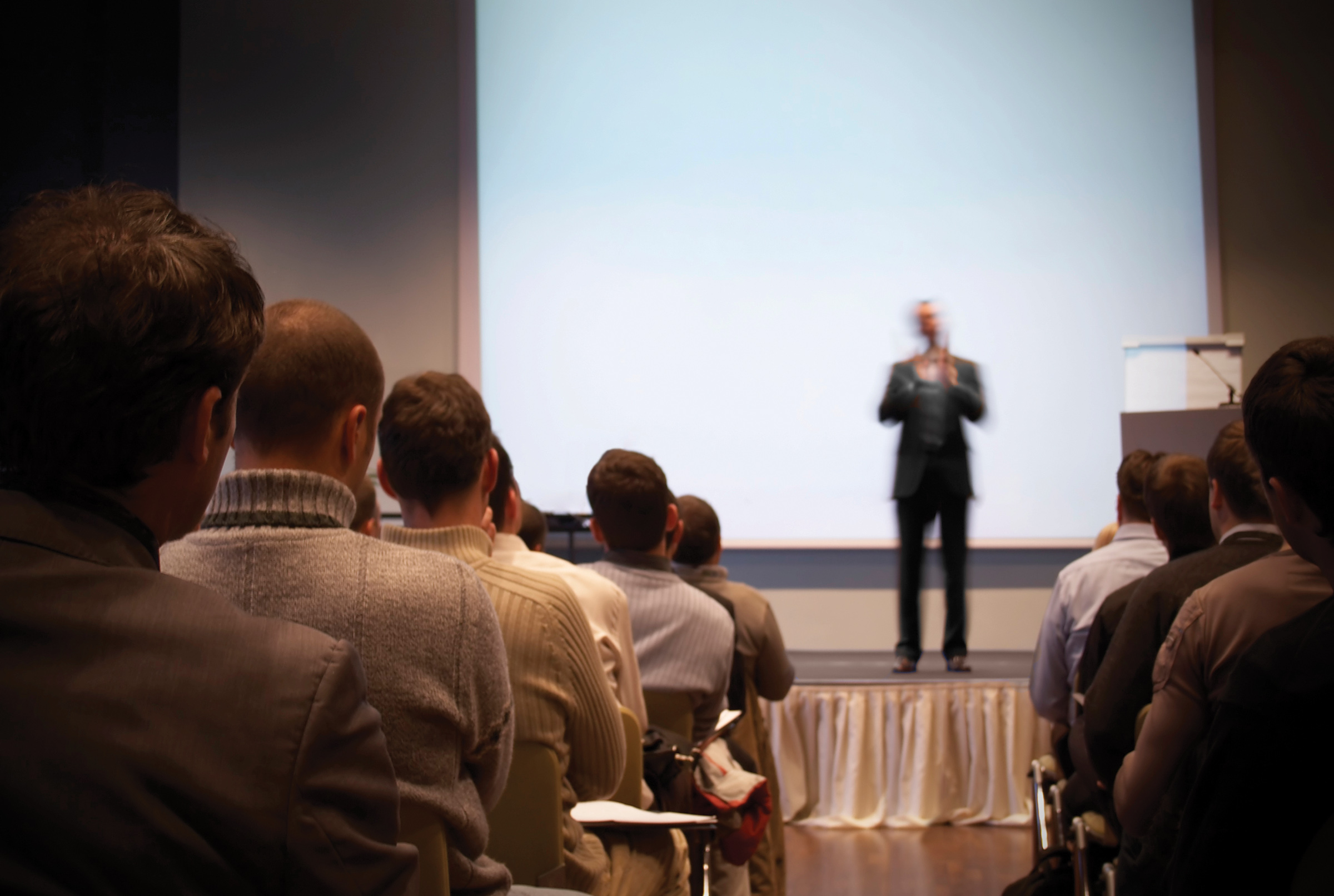 success story - professional speaker inspiring his audience, standing on stage, with screen in the background