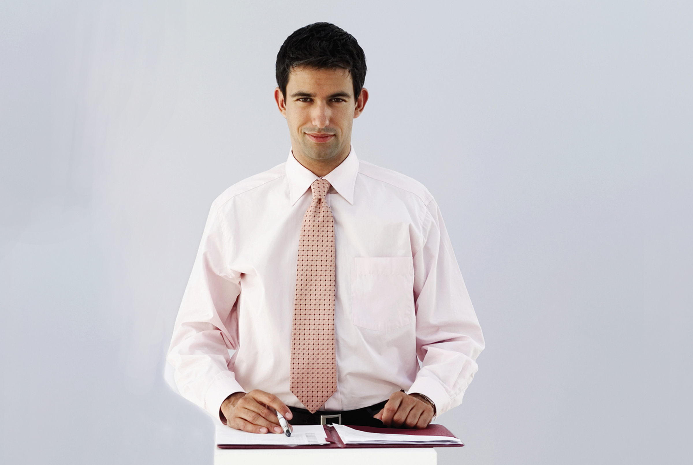 success story - executive leader looking directly into the camera, shirt and tie, with business binder under his hands