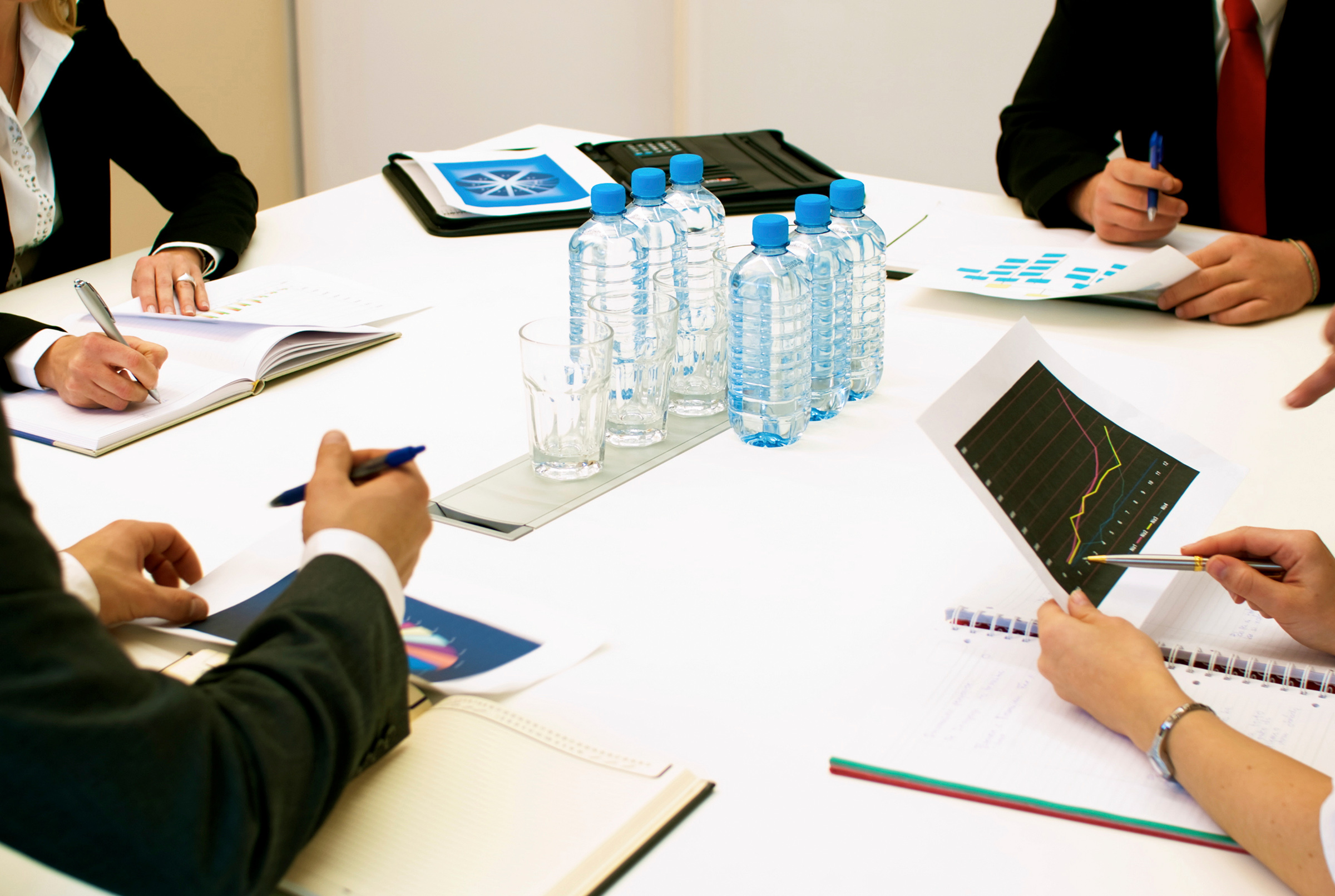 success story - group of four executives, sitting around a table discussing business plan, hands and part of torsos showing
