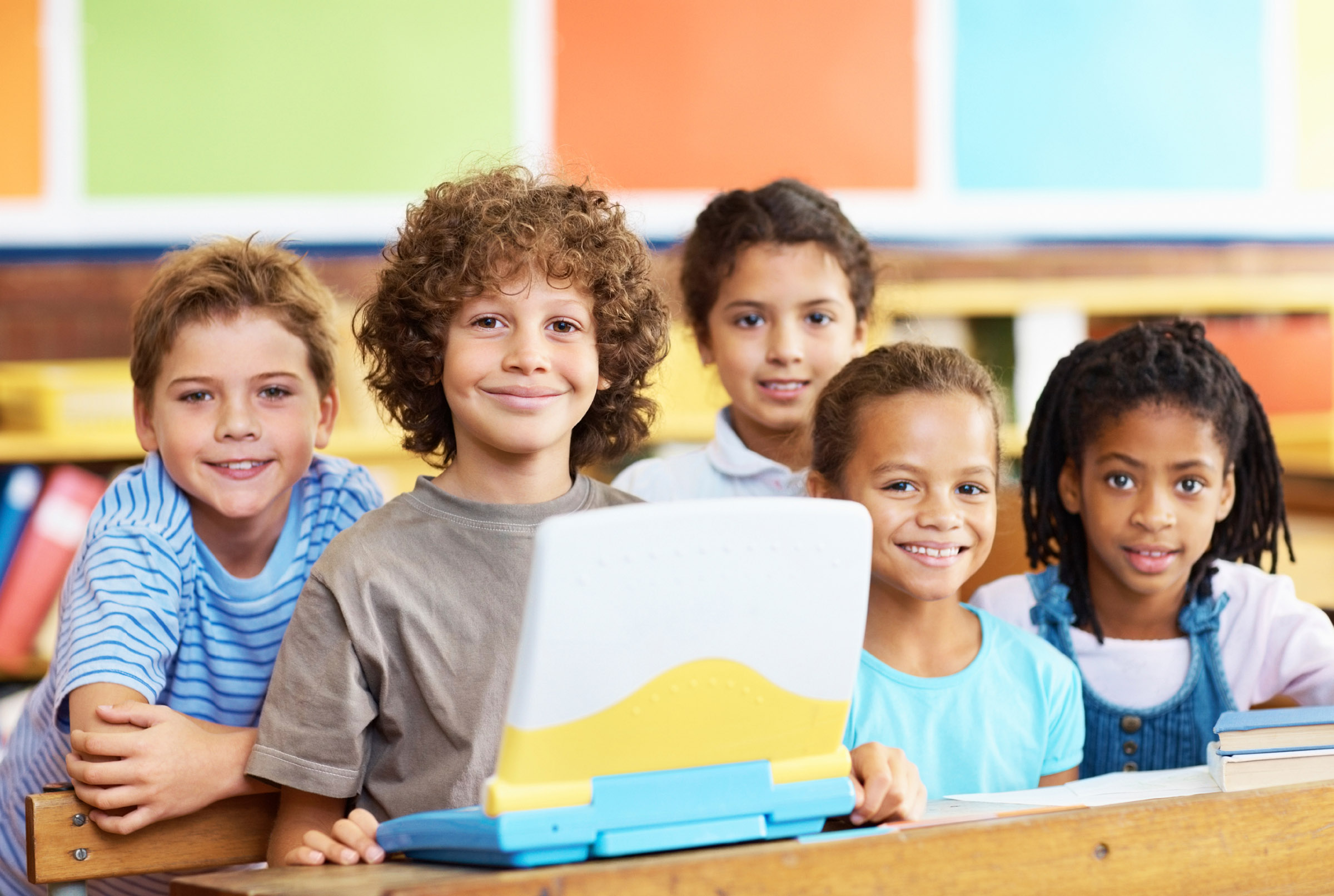 success story - group of five students around 10 years of age, smiling, around a school computer, boys and girls
