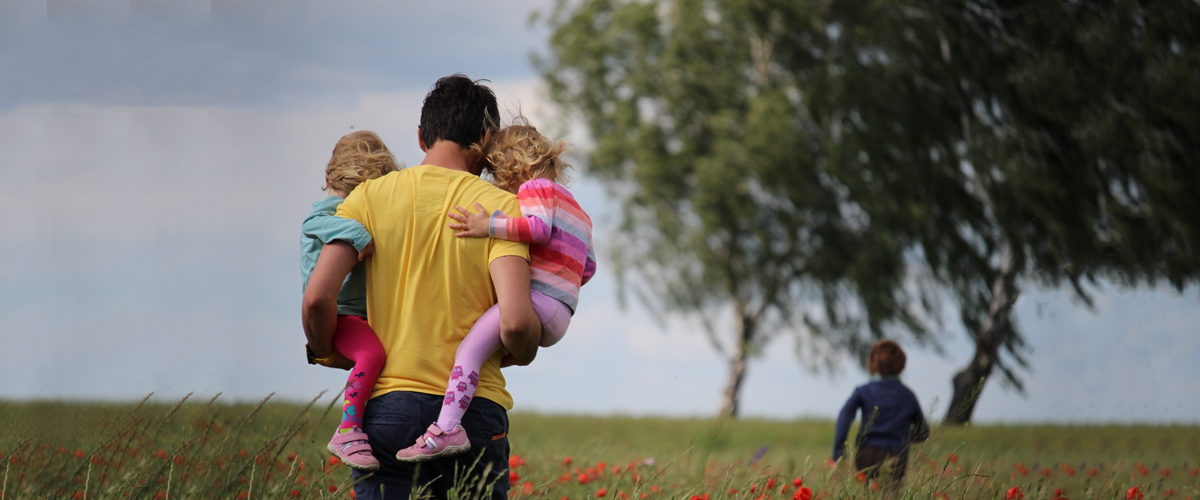 happy father's day photo with a dad and his three daughters walking in a field