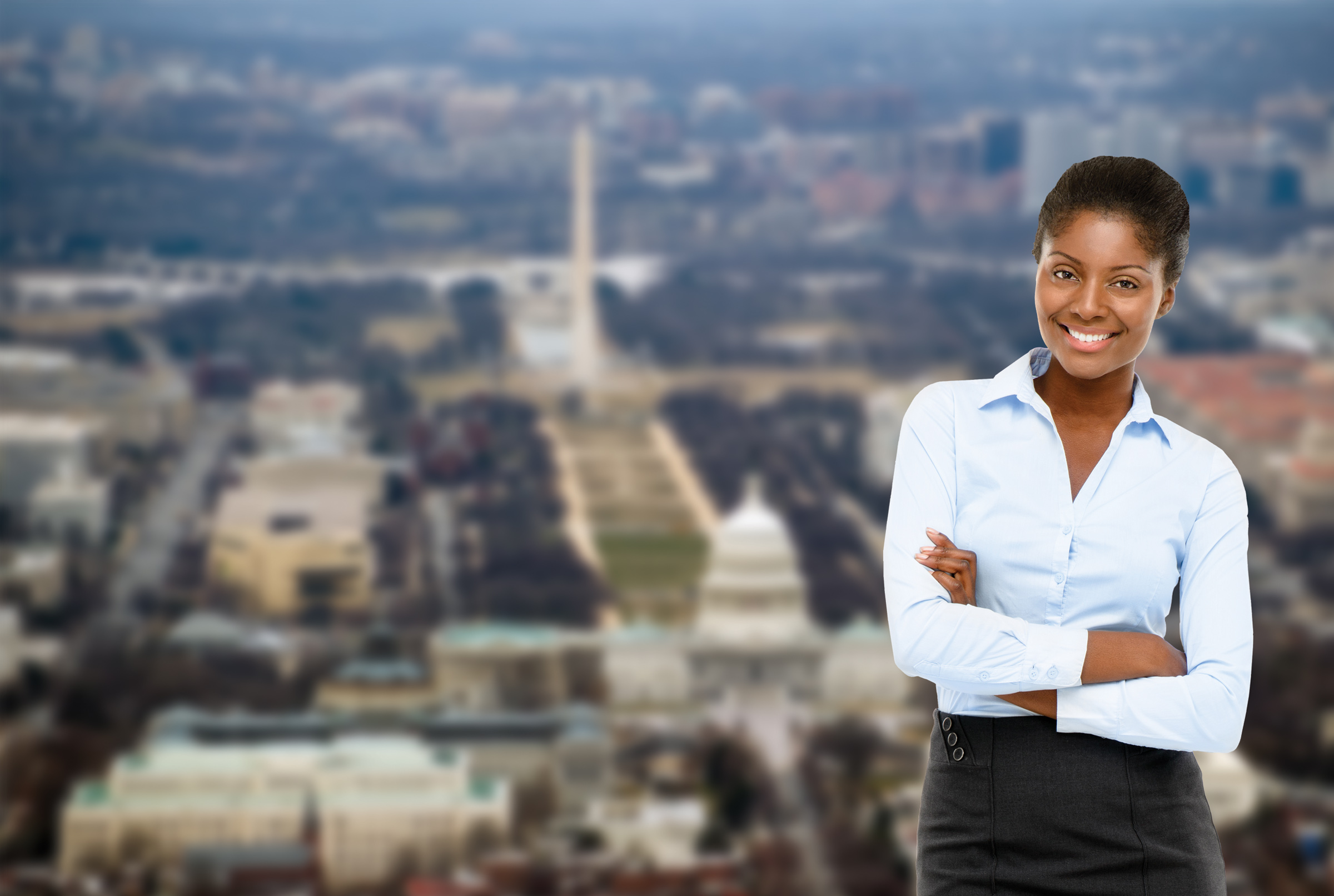 success story - confident female executive, arms crossed, smiling, with blurred background picture of the washington, dc mall area