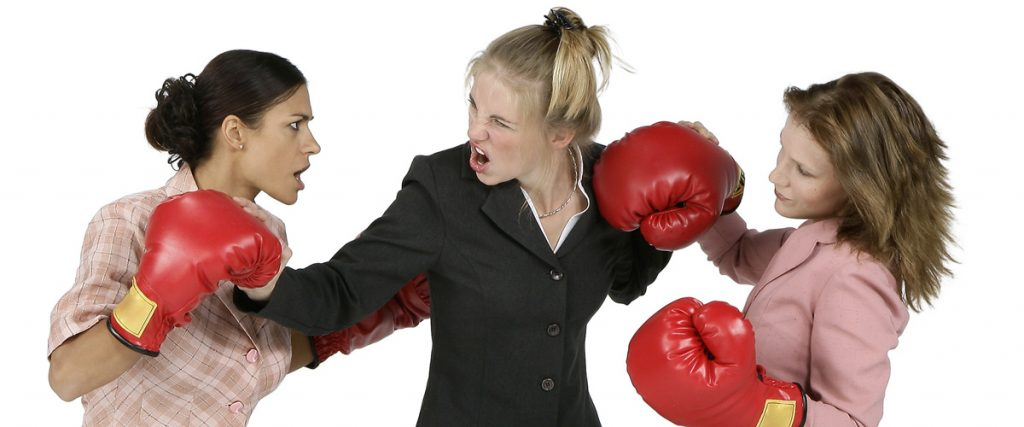 two female executives fiercly boxing, both in business suits, with obvious facial expressions of anger - serves as a metaphor on how to persuade