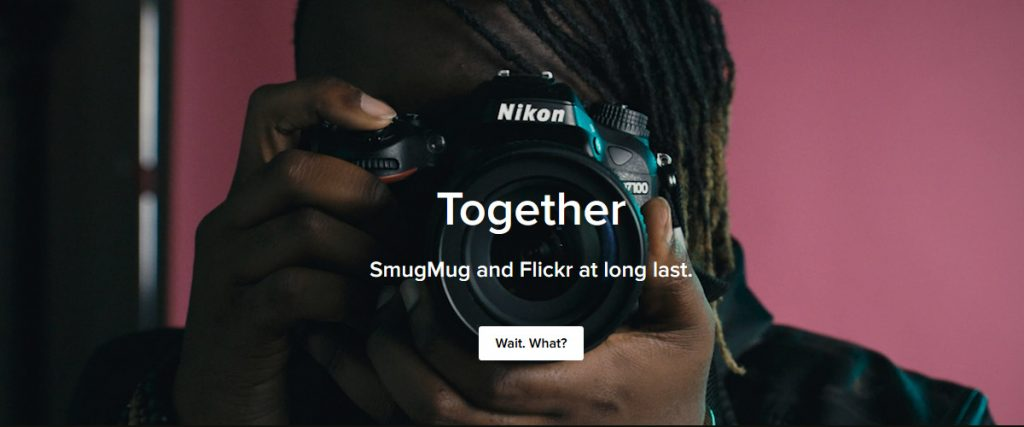 "photographer facing his lens directly toward us, big bold text ""Together, SmugMug and Flickr at long last"""