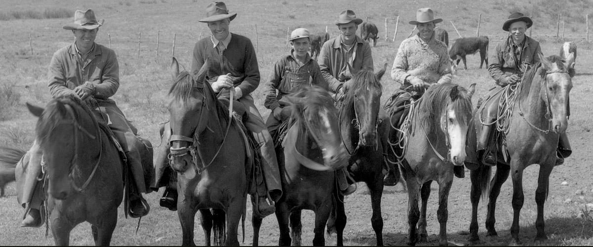 black and white, 6 cowboy ranch herders all on horseback, smiling at the camera, all supposed to work together like good consultants, like the consultants at EDS