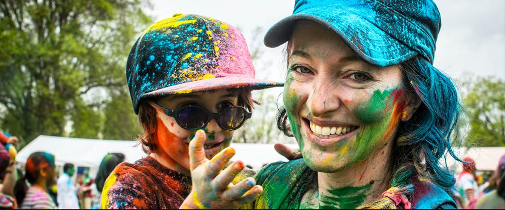 happy mothers day 2018, mom and son splattered with paint with colors from the entire rainbow