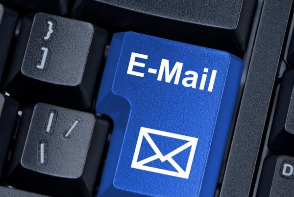 """keyboard in dark colors keys with the key """"email"""" stand out in blue - check your words before you press send"""