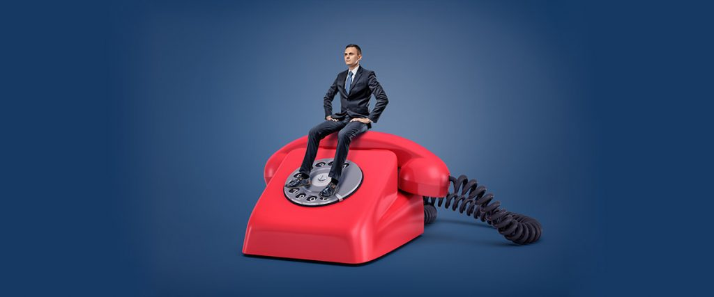 miniature executive sitting on top of a classic red telephone, having patience