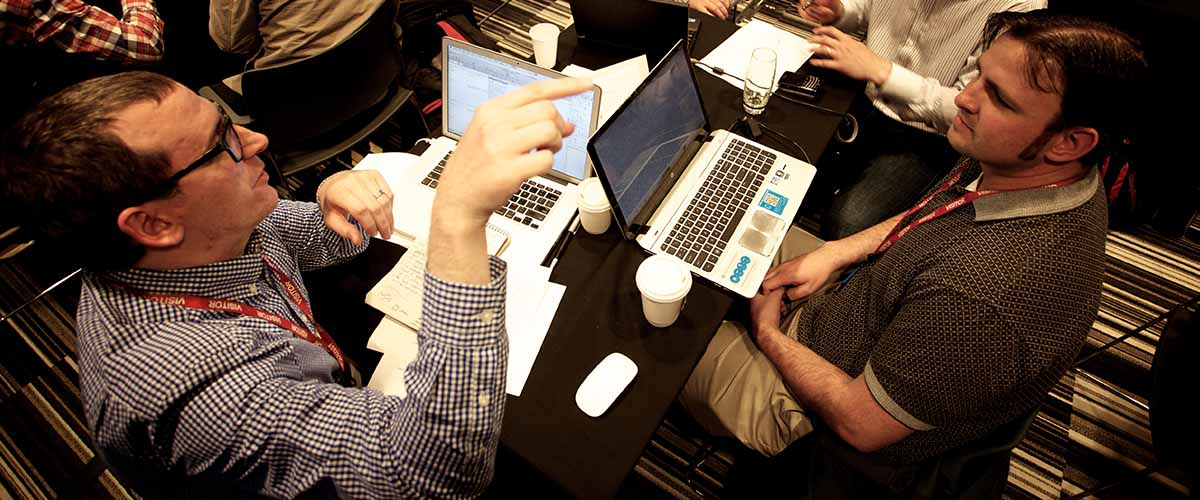 two executives, with laptops, gesturing and collaborating on innovation topic