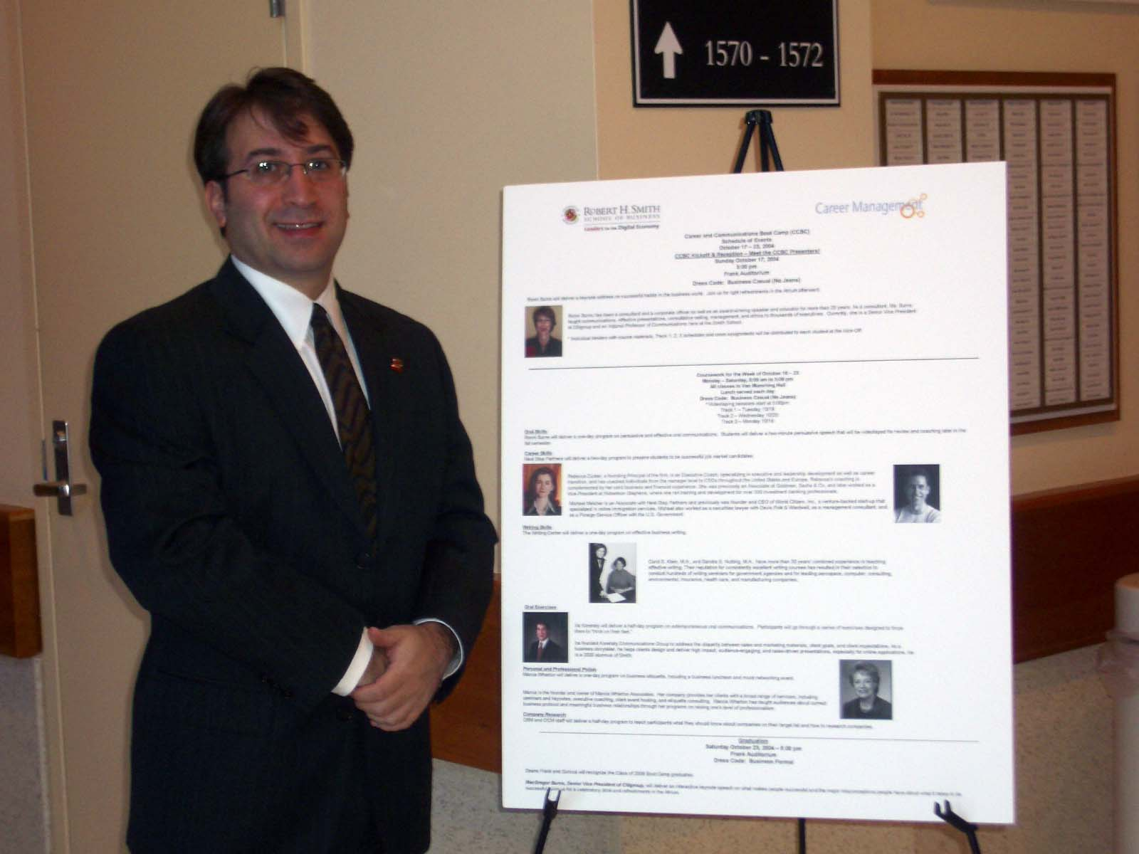 picture of ira koretsy, ceo, the chief storyteller, standing in front of the conference agenda at the robert h smith school of business at the university of maryland