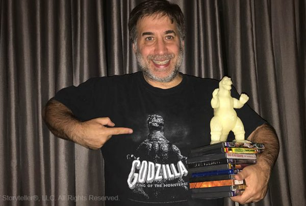 ira koretsky holding several godzilla dvds, a glow in the dark godzilla, and pointing to Godzilla on his t-shirt