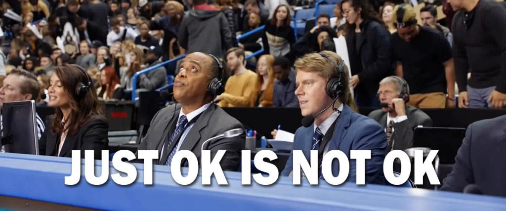 screen grab from AT&T ad, Just Ok is not Ok, two announcers sitting courtside at basketball game