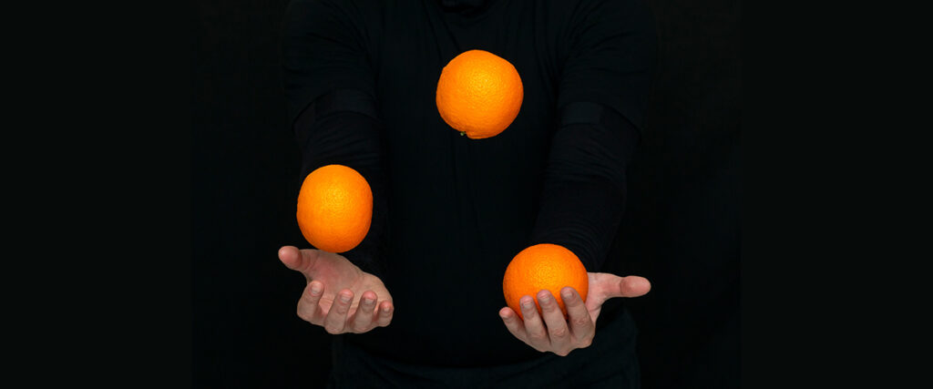 black background, near silhoutte of a man juggling three oranges, representing the challenges of project management, from our MCA Chicago Leaders to the Power of Story workshop webinar